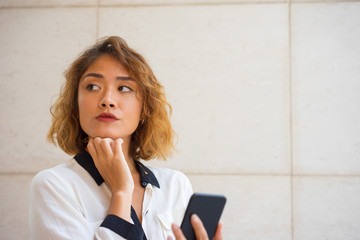 Pensive Asian Woman Holding Phone and Looking Away