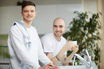 Happy gay couple looking at camera near streaming water in the kitchen