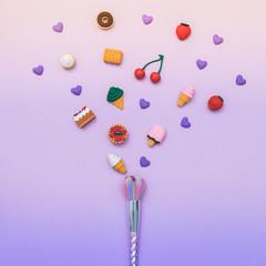one colorful make-up brush  among the dessert sweets on gradient pink and purple background