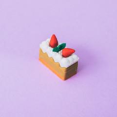 miniature piece of cake on a purple background. fashion minimal food and dessert
