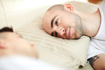 Young man with his head on pillow lying in bed and looking at his lover