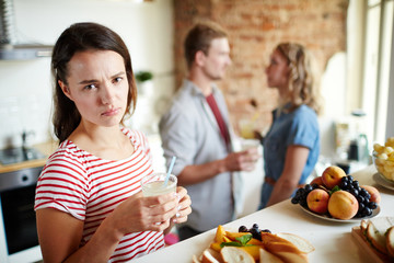 Jealous girl with homemade drink looking at camera on background of young couple having conversation