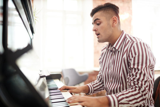 Young talented man singing while playing piano at leisure
