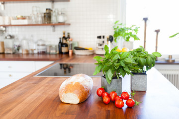 bread, tomatoes and basil ingridients on the kitchen counter top with kitchen unfocused in the background