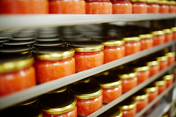 Salted red caviar in small jars standing on shelves in seafood producing plant