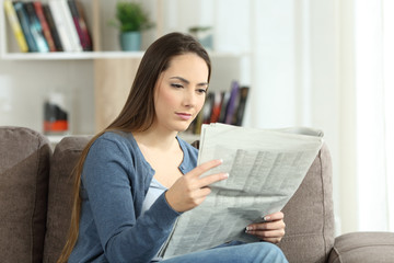 Serious woman reading a newspaper on a couch