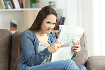 Angry woman reading a newspaper on a couch