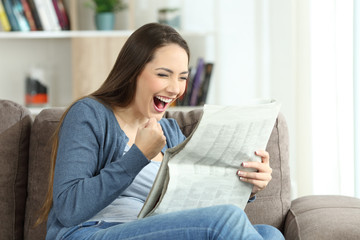 Excited woman reading a newspaper on a couch