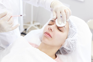 Beauty procedure. Portrait young woman receiving hyaluronic acid injection in a forehead. Painful procedure on female face. Lifting skin treatment