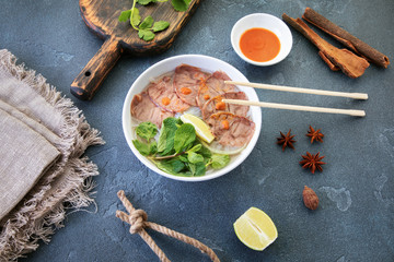 Vietnamese soup on a textured table with objects