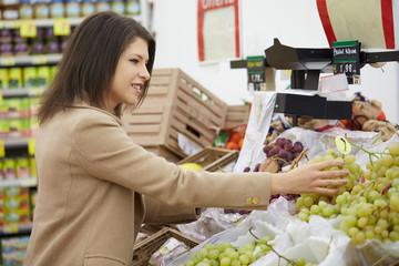 young brunette buy fruits and vegetables at supermarket