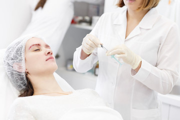 Cosmetology. Preparation in procedure Biorevitalization of the face procedure in a beauty parlour spa clinic. Doctor opens a syringe at the patient.Hands in gloves holding syringe near patient face