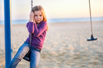 Young girl sitting on a playground swing at a sandy beach. Horizon with sea in the background.