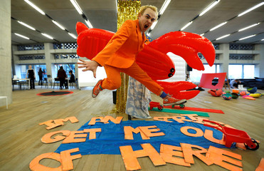 """Student artist Tom Coates from Central St. Martins college, shows off his work, """"I'm an artist get me out of here"""" at the Tate Exchange programme at Tate Modern in London"""