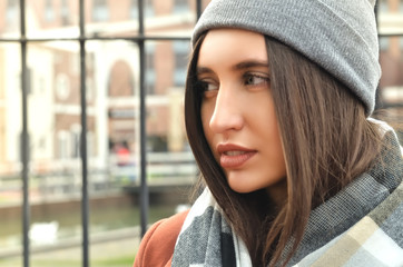 Portrait of a beautiful girl in a cap and scarf