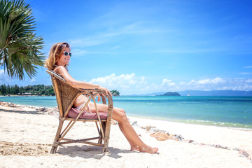 A beautiful young woman in a white bikini sits on a tropical beach. Rest, vacation, resort, beautiful life