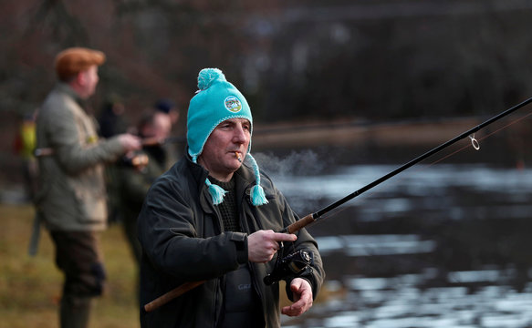 An angler smokes as he casts his line on the opening day of the salmon fishing season on the River Tay at Kenmore in Scotland