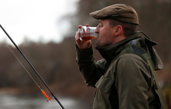 An angler has a glass of whisky on the opening day of the salmon fishing season on the River Tay at Kenmore in Scotland,