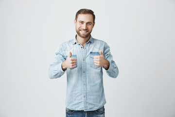 Success and achievement. Successful handsome Caucasian freelancer with stubble in denim clothes gesturing thumbs-up, looking with happy cheerful expression, achieving career goals.