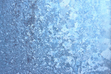 The texture of winter frost on the frozen window glass, strong frost and cold, background image in cool tones for design