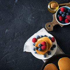 Homemade pancakes stack with berries over black texture