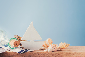 Some elements of vacation theme, shell, botle and toy ship on blue backround, copy space
