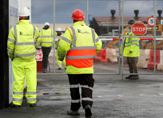 Workers stand outside Carillion's Midland Metropolitan Hospital construction site after the company went into liquidation, in Smethwick