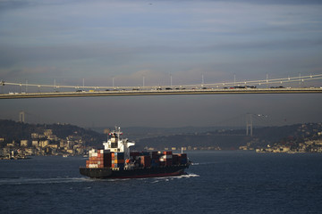 A container ship is passing under The Bosphorus Bridge in a sunny day at Istanbul. Also The Fatih Sultan Mehmet Bridge is visible at the background too.