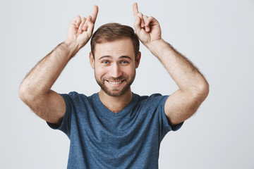 Handsome european young male with beard and pleasant smile, makes gesture with index finger, points upwards, shows something above his head, isolated against gray background. Positive emotions