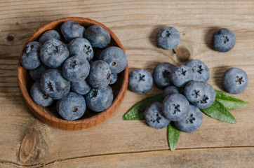 blueberries in wooden bowl  and on wooden background