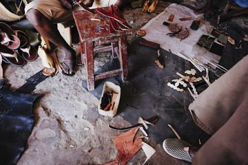 Men working into the shoes shop. In this place, they produce a typical kenyan shoes with leather and other materials.