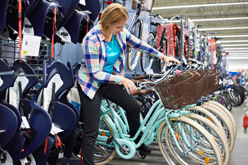 Woman chooses bicycle in shop