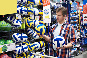 Man chooses volleyball in sports shop