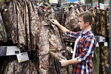 Man chooses clothes for hunting in sports shop