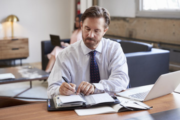 Businessman at desk writing notes