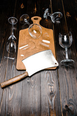 high angle view of broken wineglasses and axe with wooden board on table
