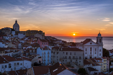 View of the Alfama neighborhood from the Portas do Sol viewpoint at sunrise in Lisbon, Portugal; Concept for travel in Portugal, visit Portugal and most beutiful places in Portugal