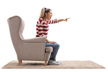 Angry young woman sitting in an armchair and arguing
