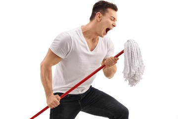 Young man singing on a mop