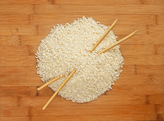 raw rice and chopsticks on bamboo board