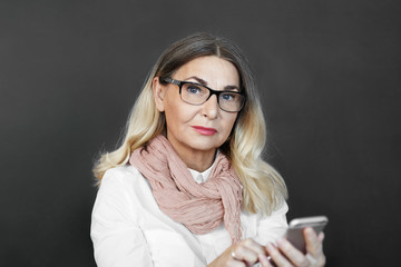 Stylish mature female teacher wearing scarf over white formal shirt and black spectacles typing text message on mobile phone during break at college, looking at camera with serious facial expression
