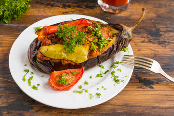 Eggplant stuffed with minced meat and baked with fresh tomatoes and bell peppers on white plate on wooden rustic table.
