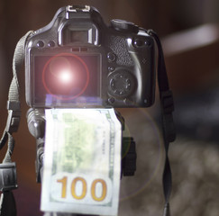 a camera, under it 100 dollars, in focus. in the background the girl does not focus. The concept of earning in a photo