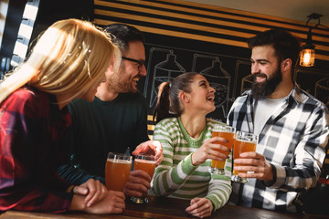 Smiling young people drinking craft beer in pub