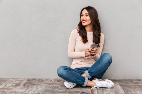 Portrait of smiling woman with red lips typing text message or scrolling in internet using mobile phone sitting in lotus pose over gray background