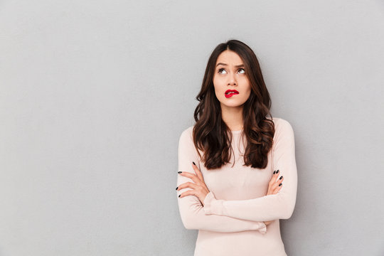 Portrait of young woman biting her red lips standing with arms folded over gray background being confused or frustrated