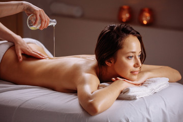 Relaxed woman having a massage with oil in a spa