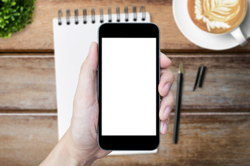 Hand is holding smartphone with blank screen over the wood office table.
