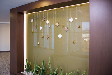 glass wall decorated with a garland and Christmas-tree toys