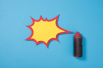 top view of spray paint in can and empty paper speech bubble isolated on blue